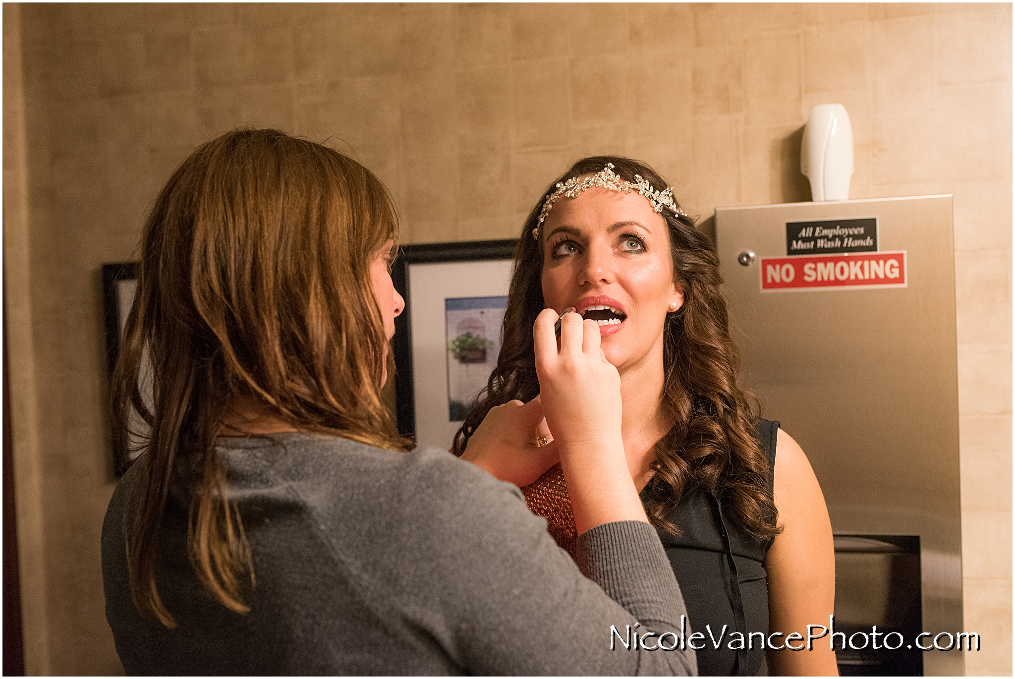 The bride gets last minute touch ups in the bathroom at Bookbinders.