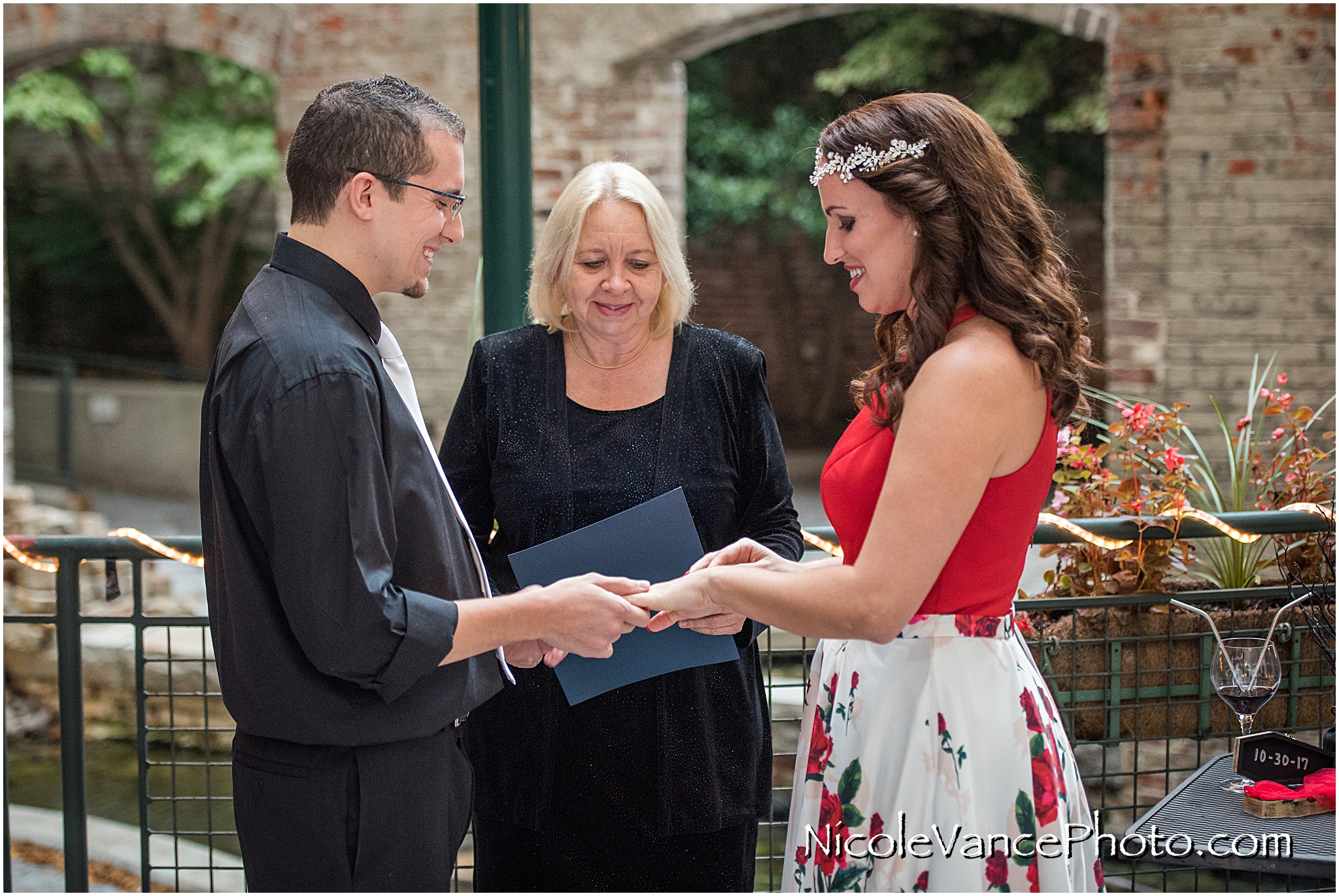 Exchanging rings during their wedding ceremony at Bookbinders on the back patio.