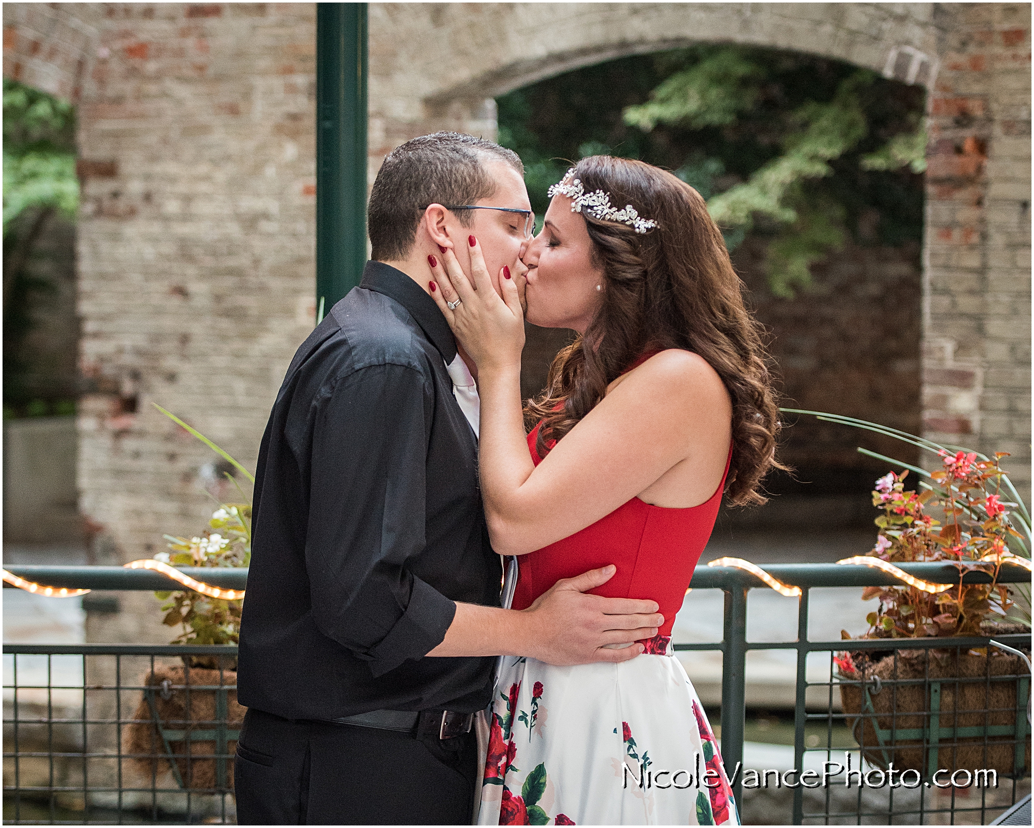 First kiss during their wedding ceremony at Bookbinders on the back patio.