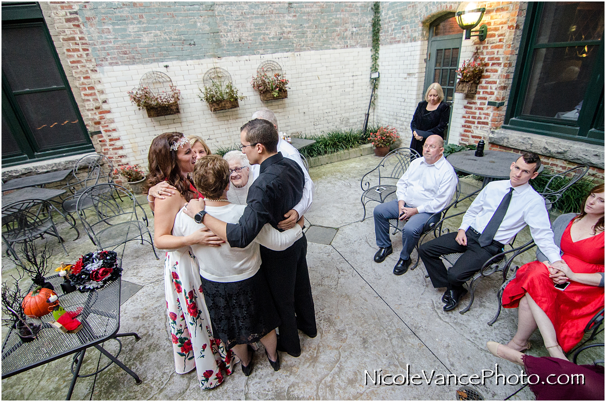 The whole family embraces after a wedding ceremony at Bookbinders on the back patio.