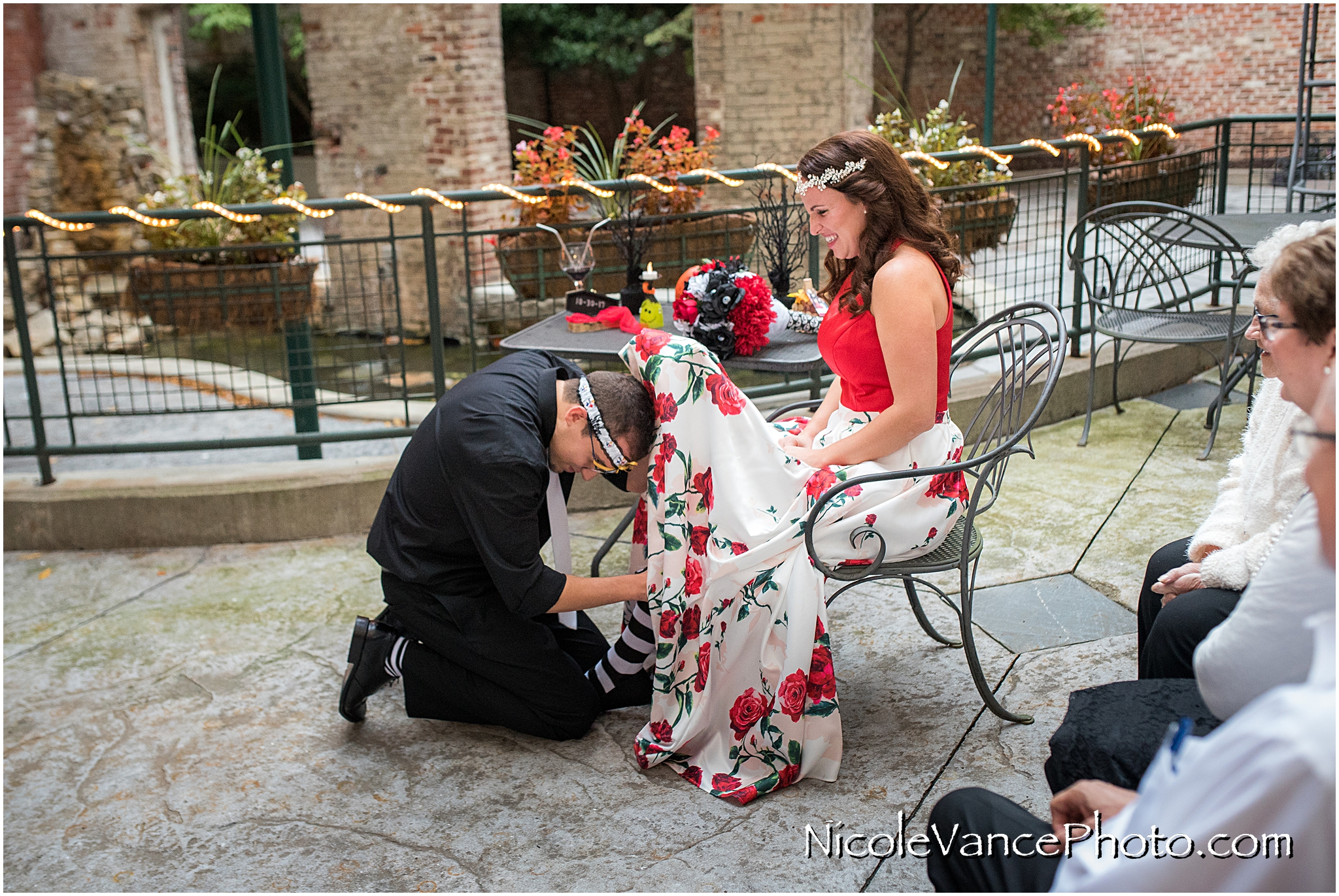 The groom retrieves the garter at Bookbinders on the back patio.