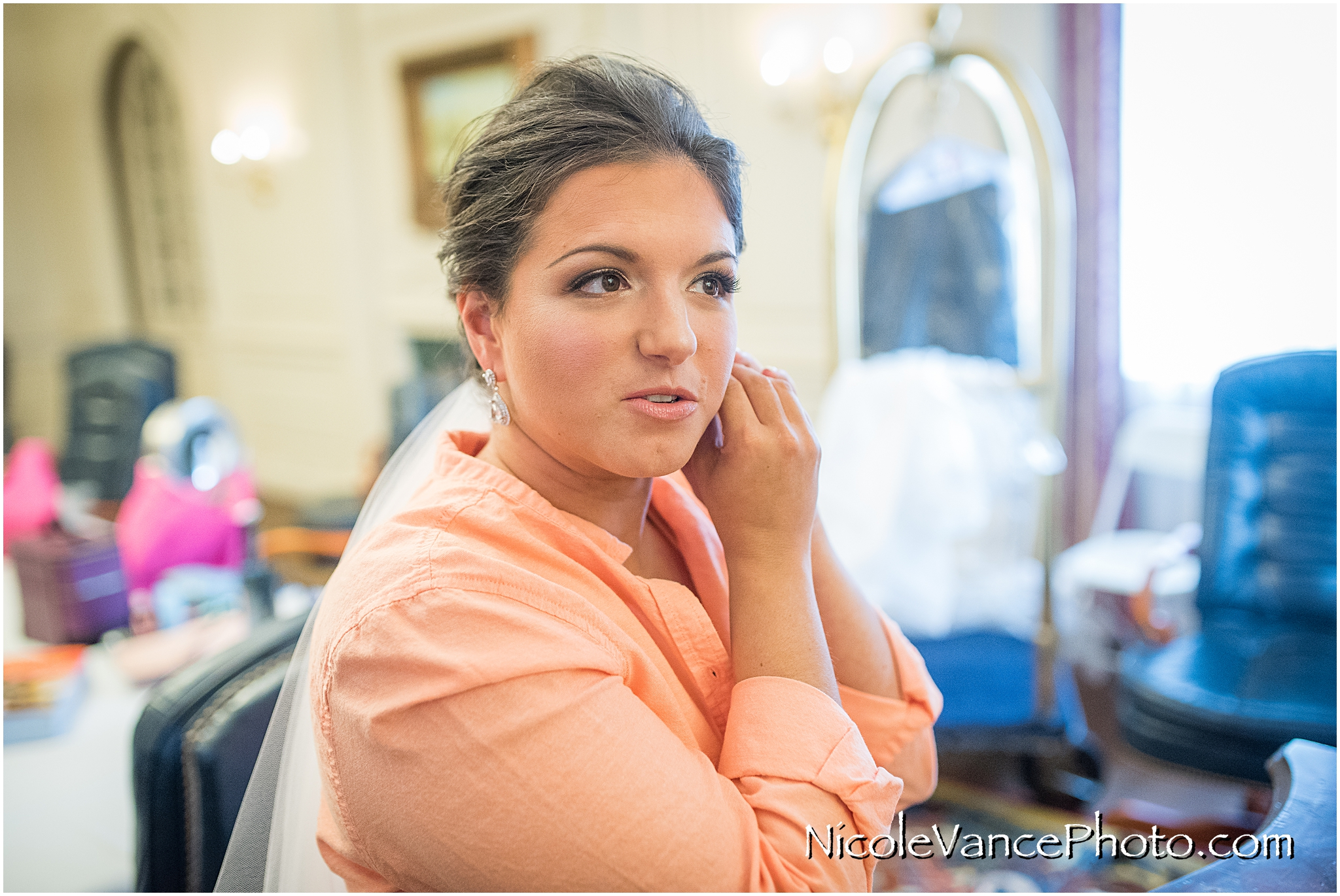 The bride puts on her earrings in the conference rooms at Virginia Crossings.