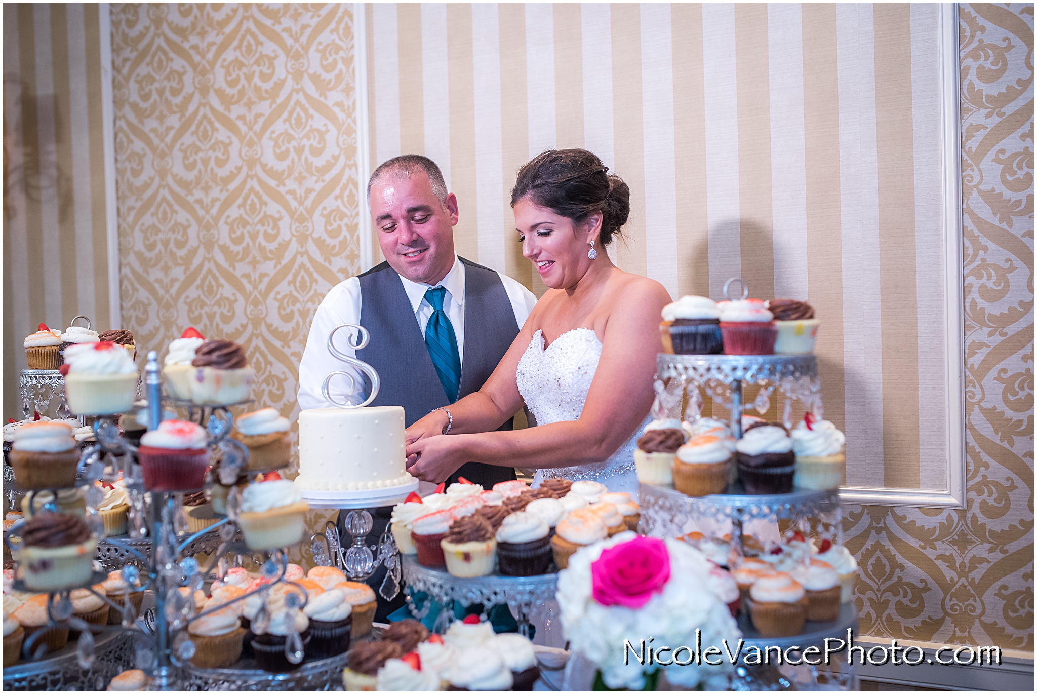 The bride and groom cut their wedding cake provided by Pearls at Virginia Crossings.