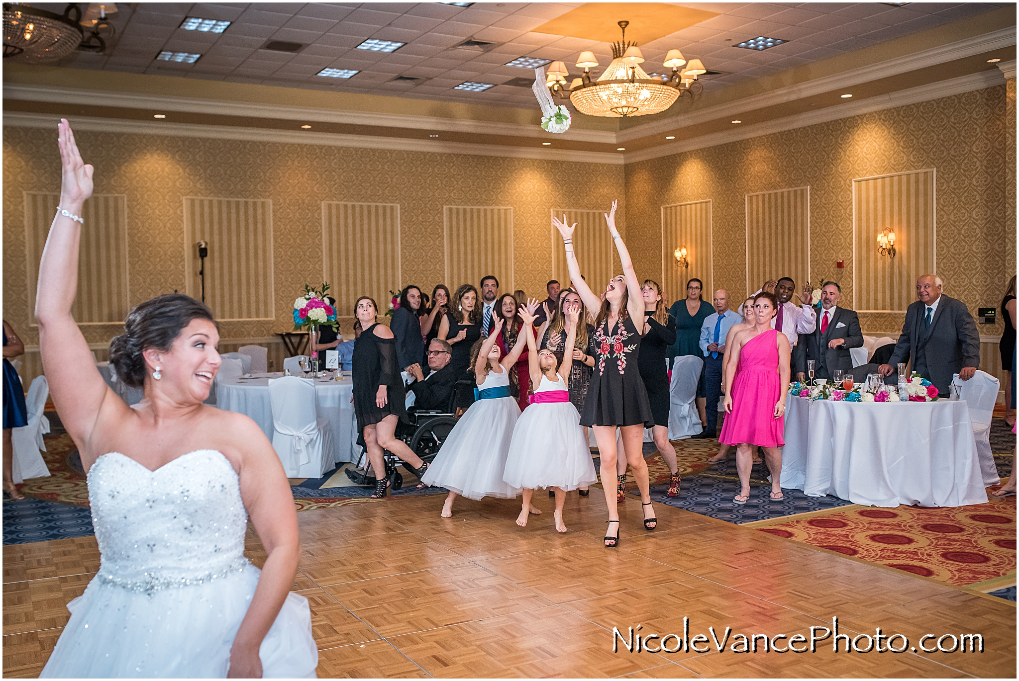 The bride tosses the bouquet at her reception at Virginia Crossings.