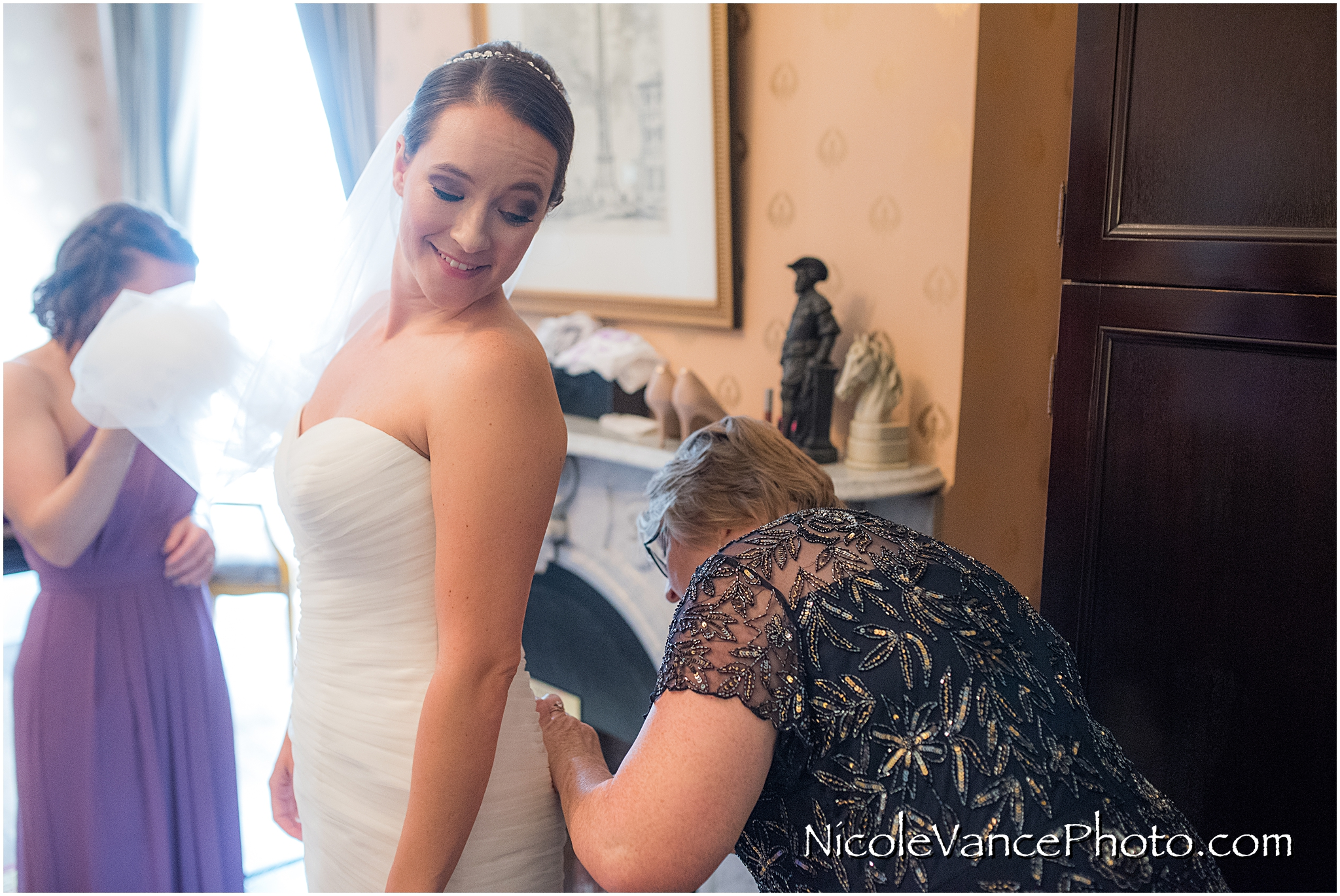 The bride's mom carefully fastens her buttons as she helps her daughter get ready.