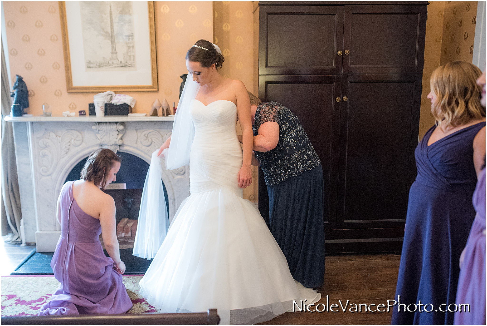 The bride's mom carefully fastens her buttons as she helps her daughter get ready at the Bridal Suite at the Linden Row Inn in Richmond, VA.