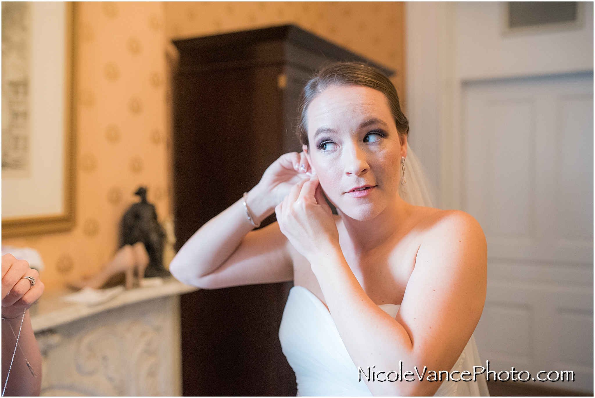 The bride puts on her earrings in her room at the Linden Row Inn.