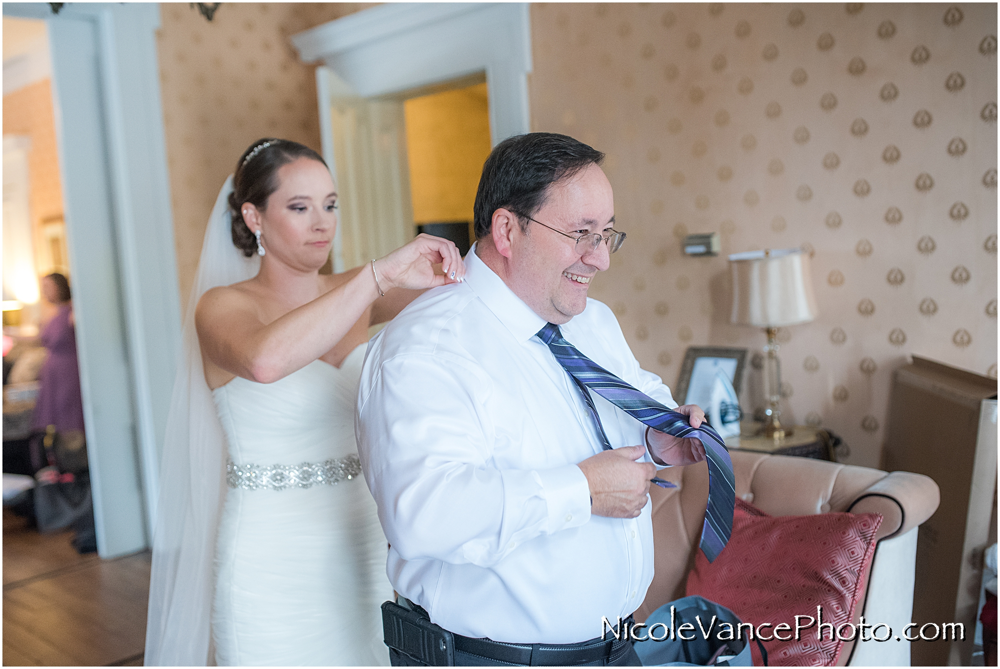 The bride helps her dad with his tie... she is waiting for his to see the special embroidery underneath the tie she purchased for him as a gift.