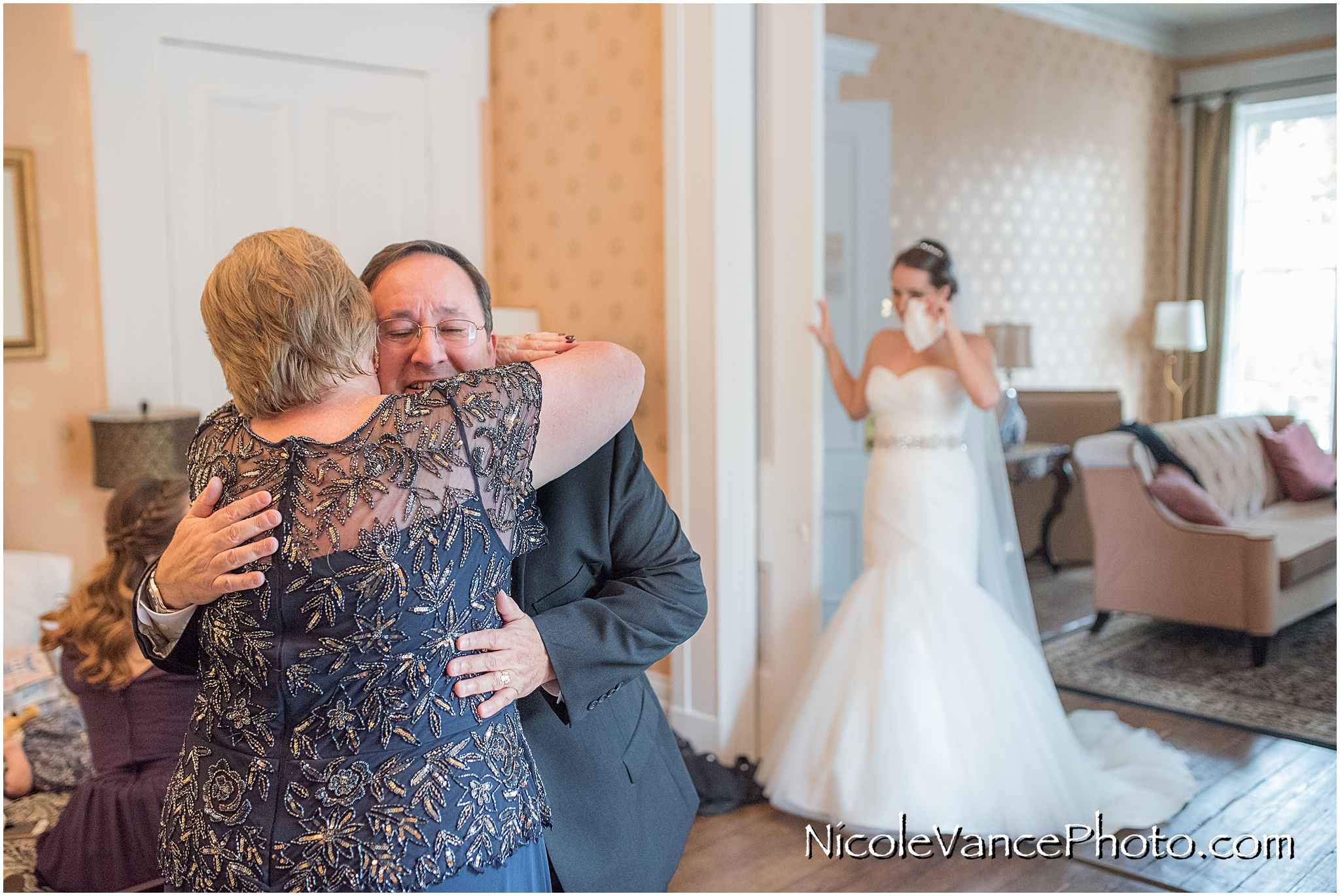 Mom and dad embrace and share a moment together as they share their happiness for their daughter on her wedding day.