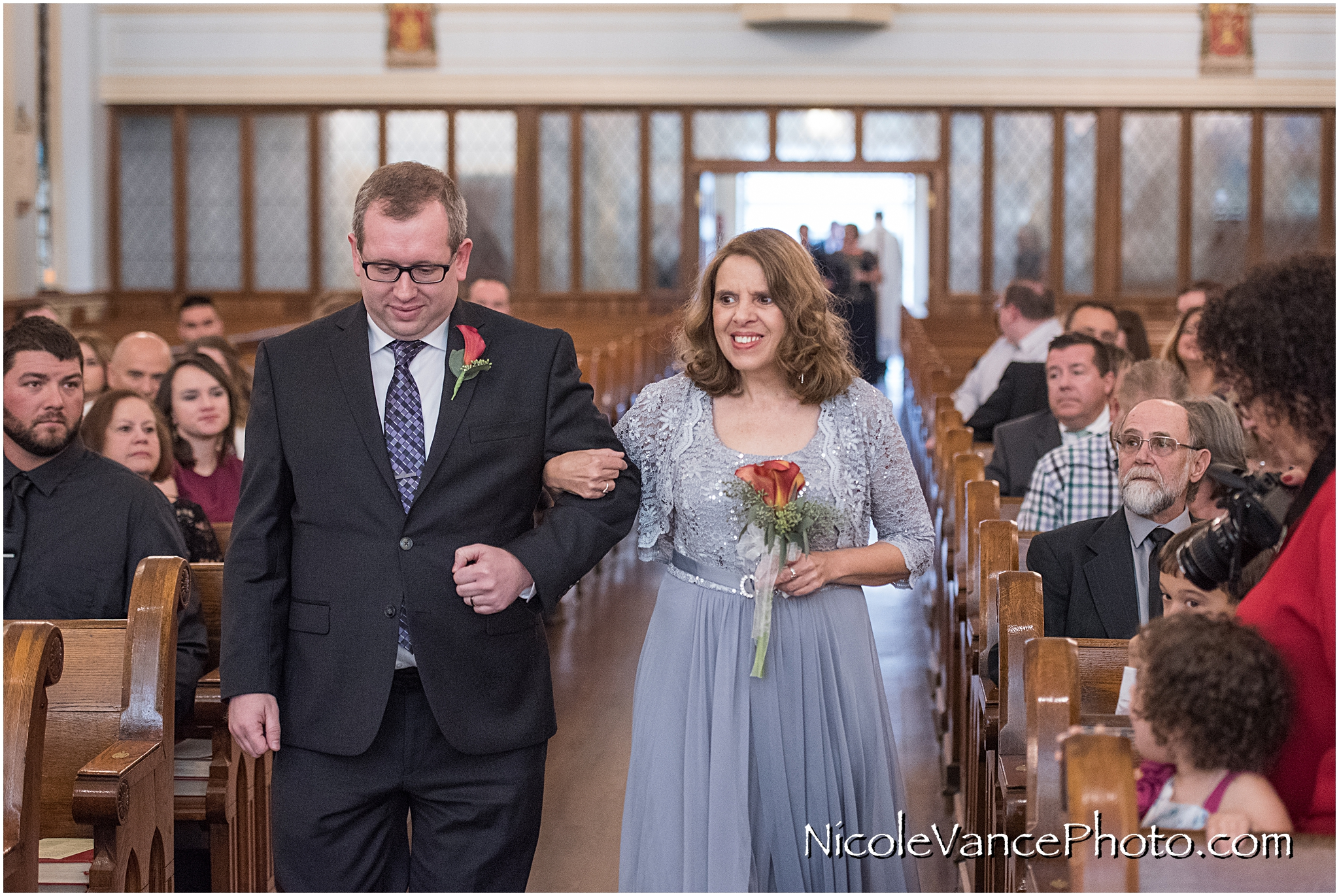 The grooms mom comes down the aisle at St Peter's Catholic Church.