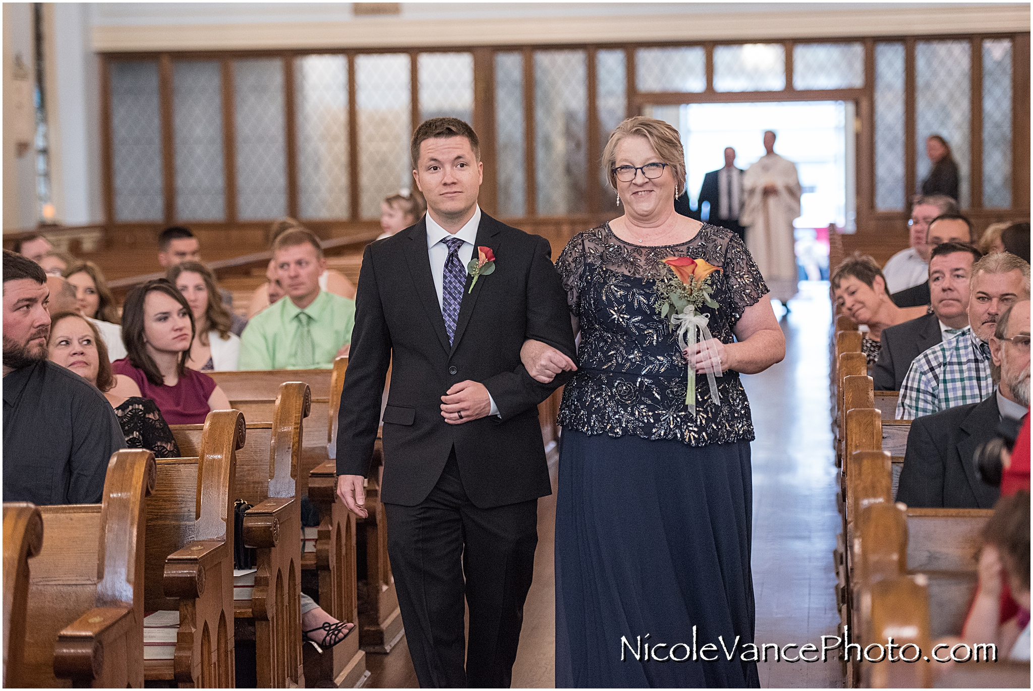 The bride's mom comes down the aisle at St Peter's Catholic Church.
