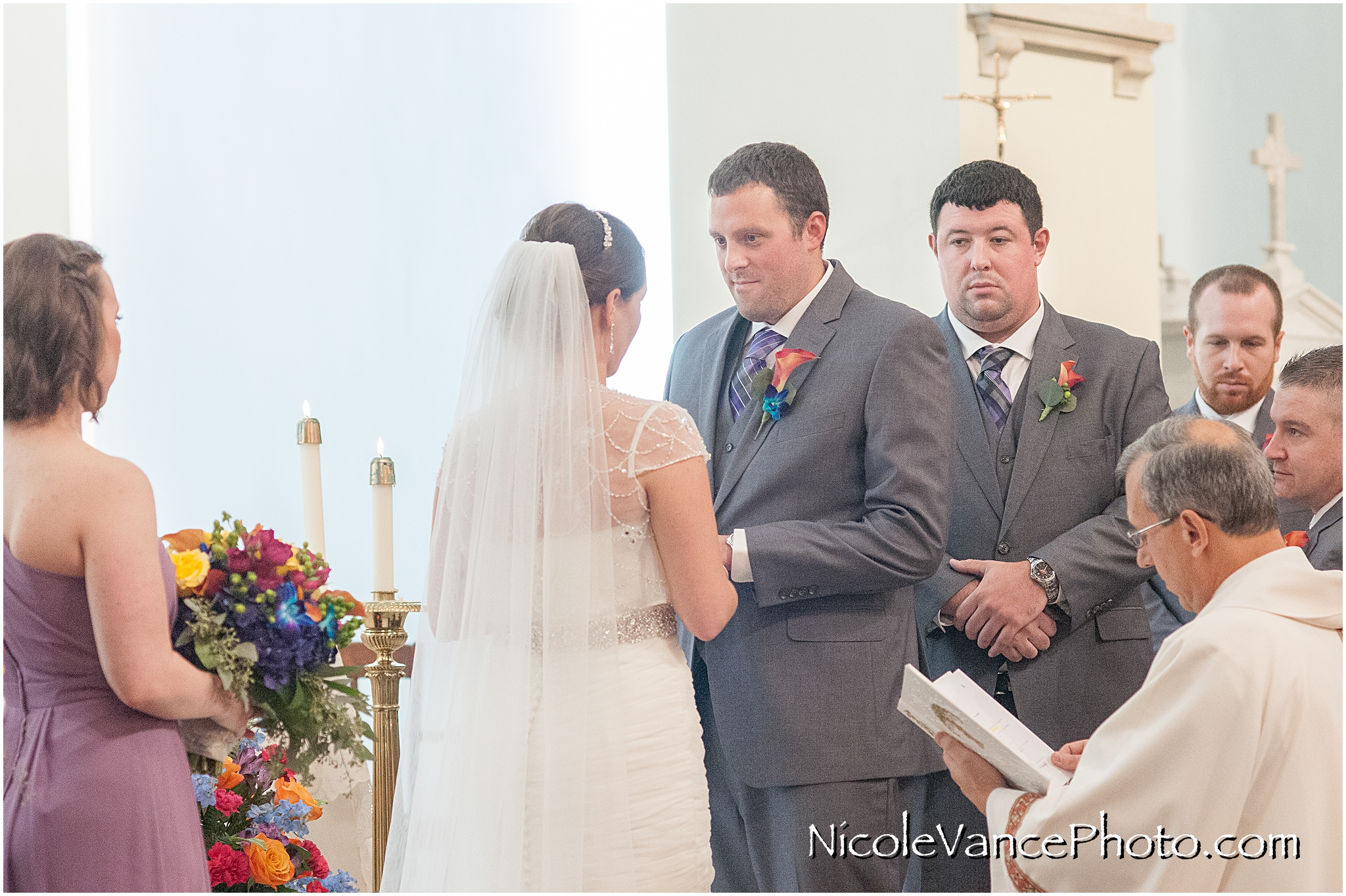 The bride and groom exchange vows and rings during their wedding ceremony at St Peter's Catholic Church in Richmond, VA.