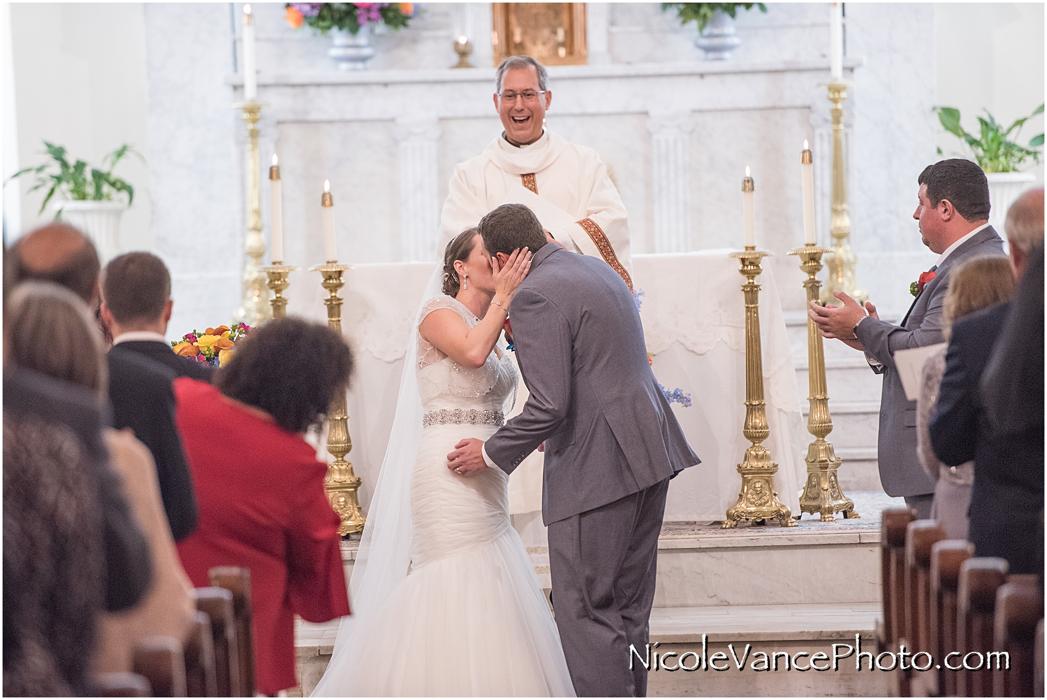 The bride and groom's first kiss during their wedding ceremony at St Peter's Catholic Church in Richmond, VA.