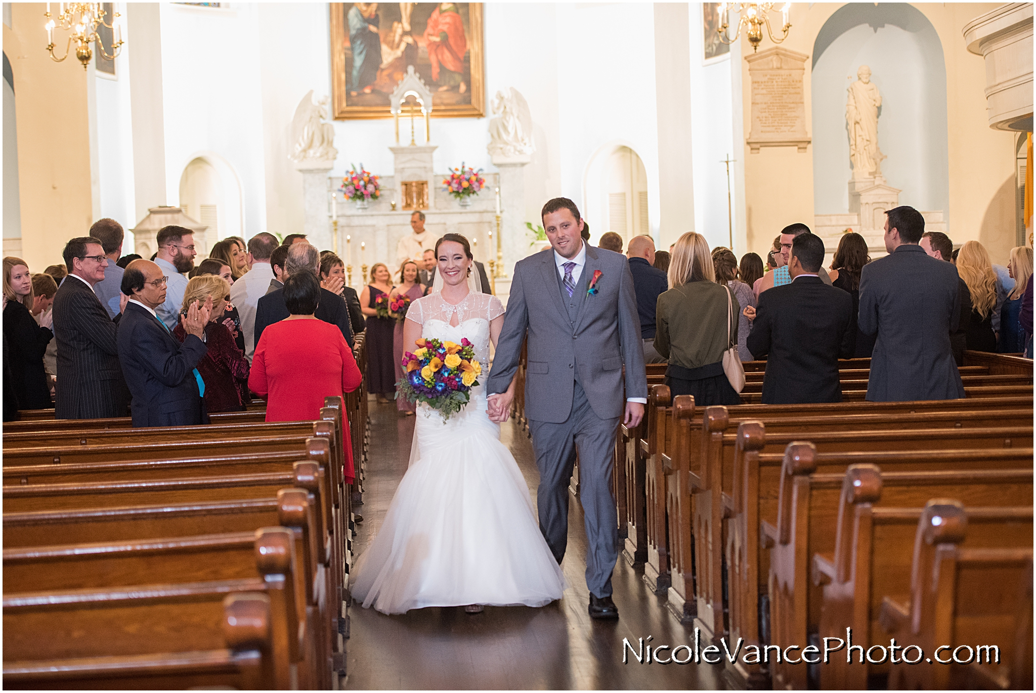 The newlyweds process back down the aisle of St Peter's Church in Richmond VA.