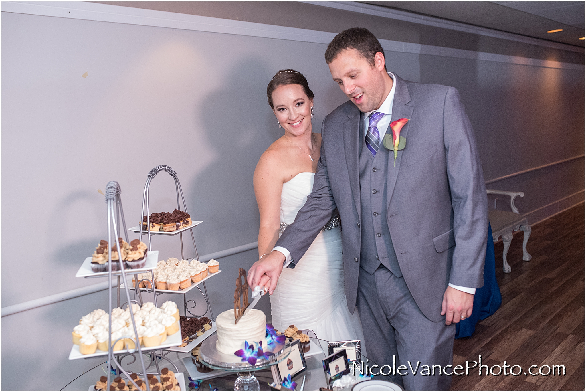 The bride and groom cut their cake, provided by Kakealicious at the reception at The Brownstone.