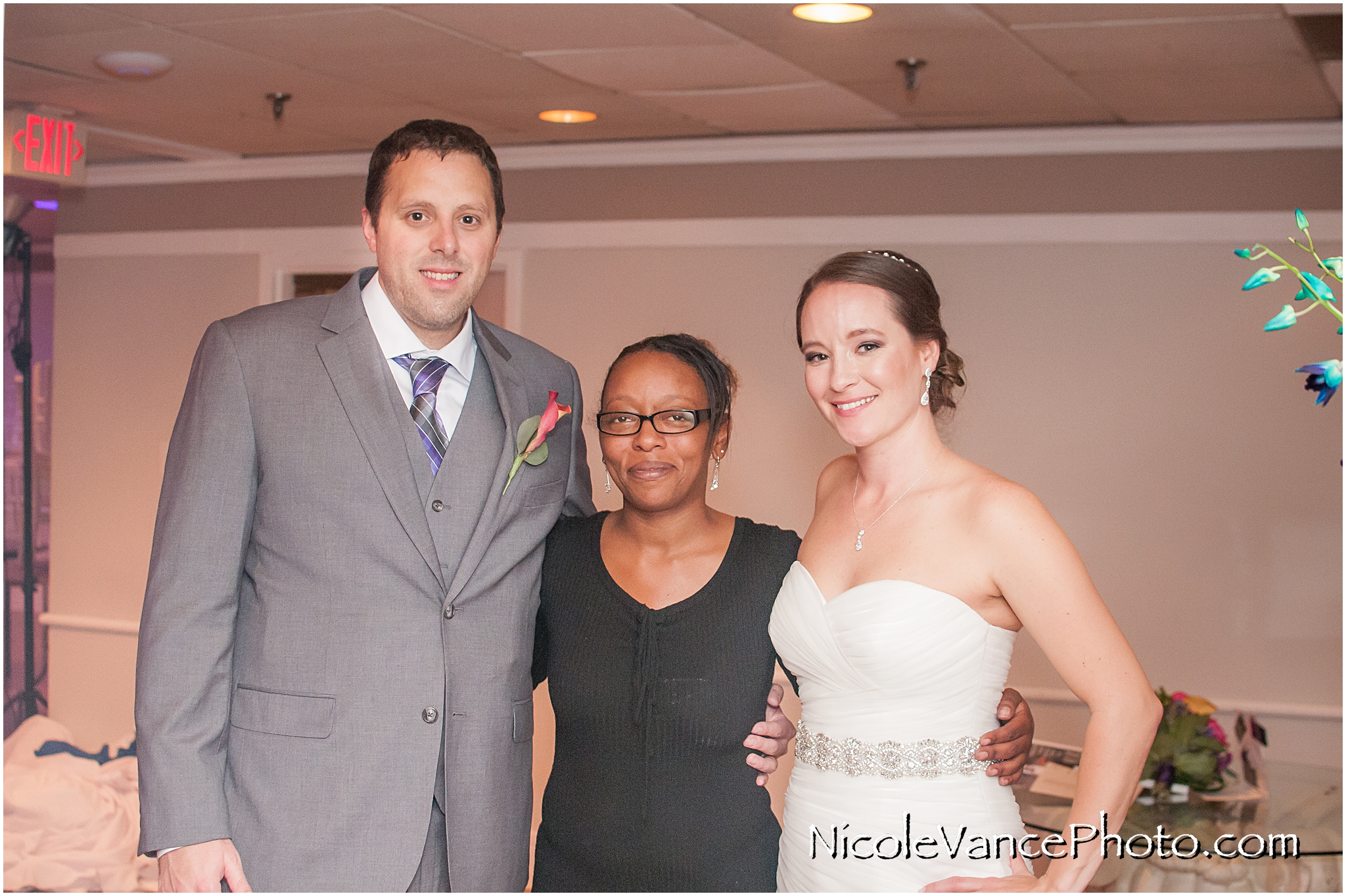 The bride and groom pose with their onsite wedding planner at The Brownstone in Richmond, Virginia.