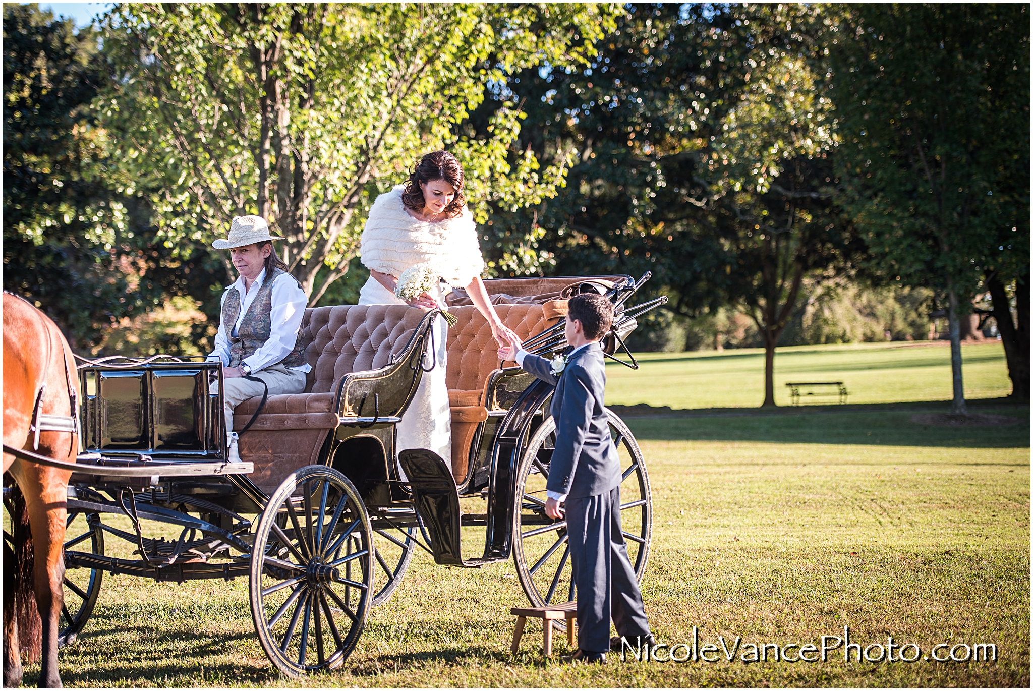 The bride arrives via horse drawn carriage at her wedding ceremony at Maymont Park in Richmond Virginia.