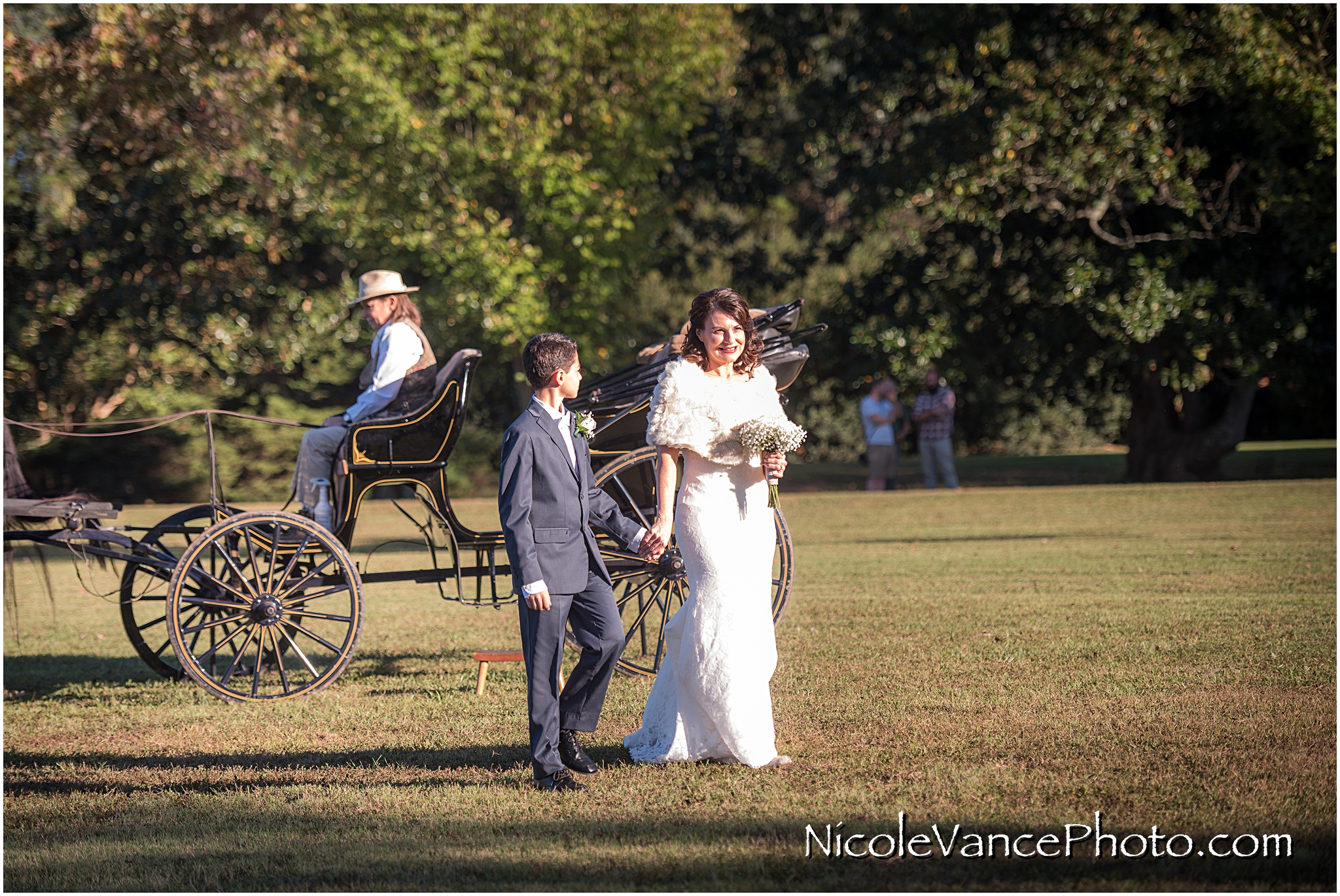 The bride is escorted to the ceremony by her son at Maymont Park.