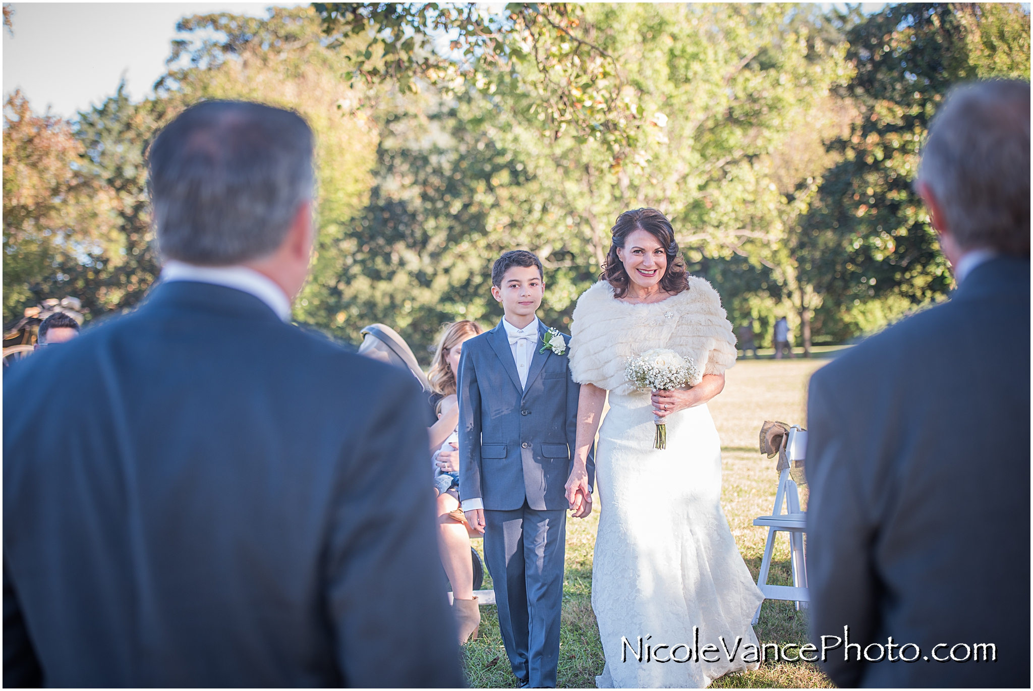 The bride walks down the aisle and smiles at her groom at Maymont Park.
