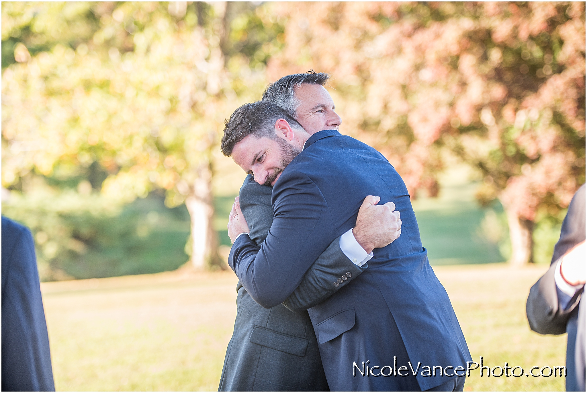Father and son embrace after the wedding ceremony.