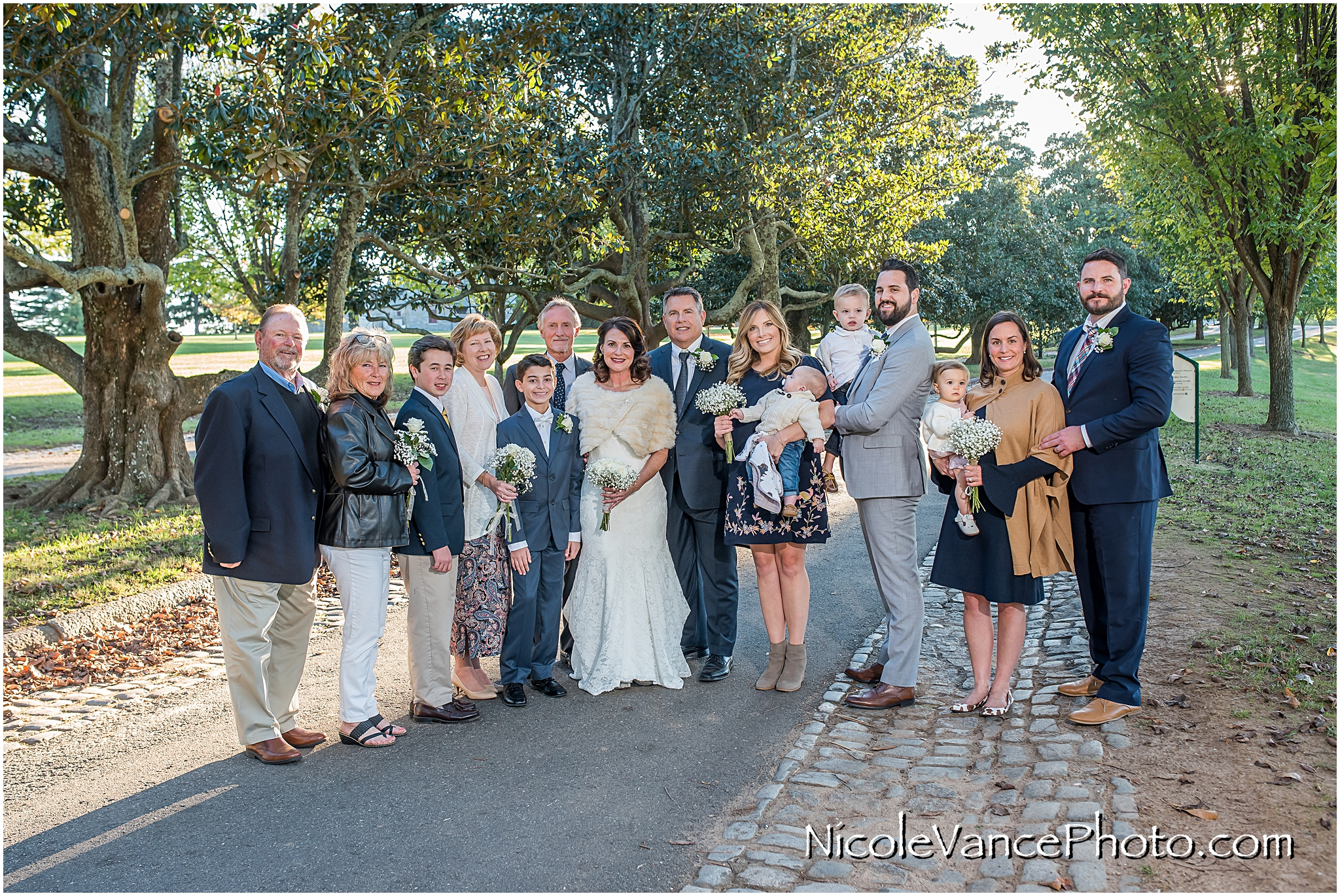 The bride and groom pose with all the guests in attendance at Maymont Park in Richmond, Virginia.